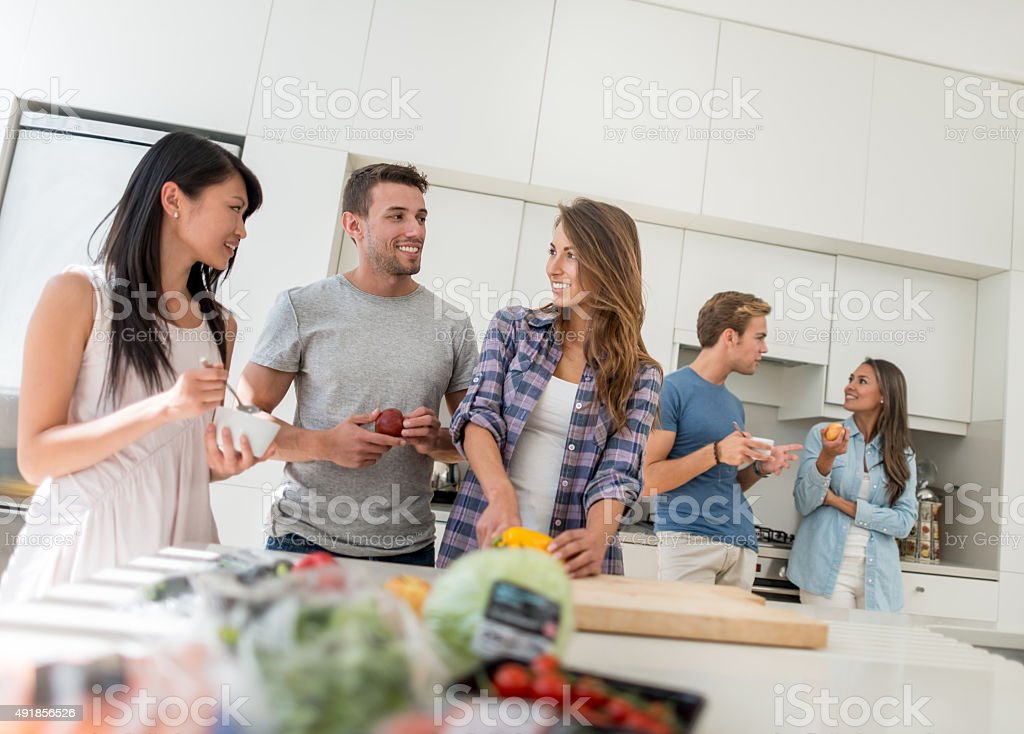 Friends living together and cooking at home stock photo