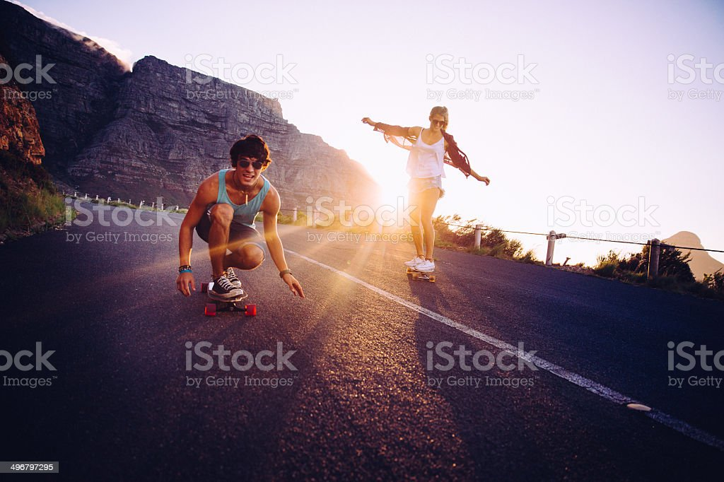 Friends longboard skating on road sunset stock photo