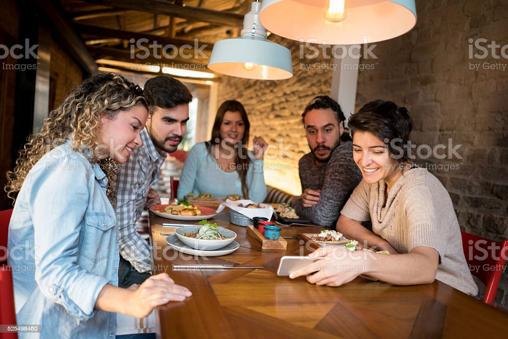 Friends looking at a cell phone at a cafe stock photo