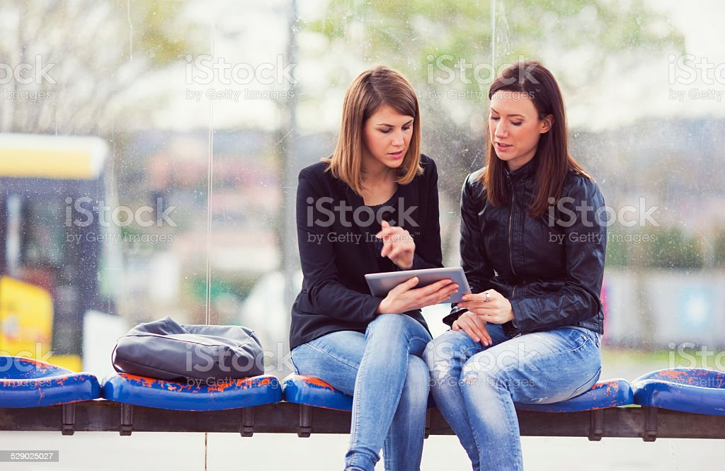 Friends looking at digital tablet on the bus station stock photo