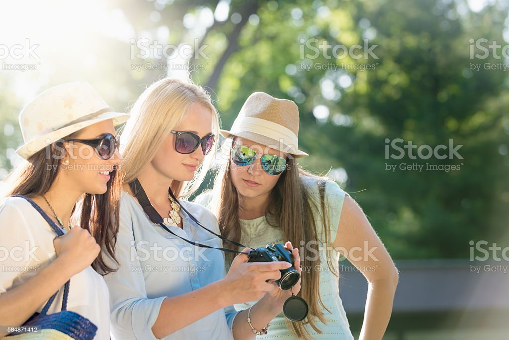 Friends looking at photos on their camera at summer vacation stock photo