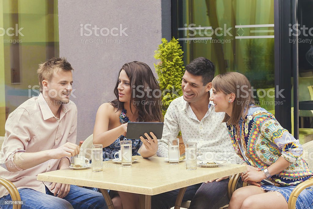 Friends looking at pictures on tablet in cafe stock photo