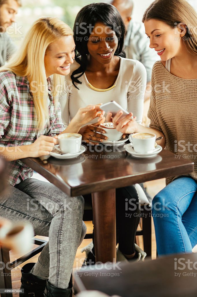 Friends looking at smart phone stock photo