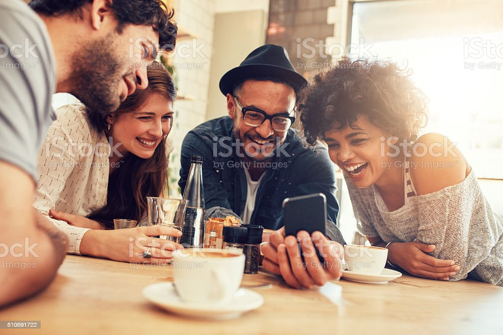 Friends looking at smart phone while sitting in cafe stock photo