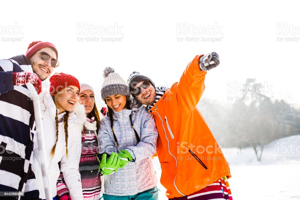 Friends looking at snowy field stock photo