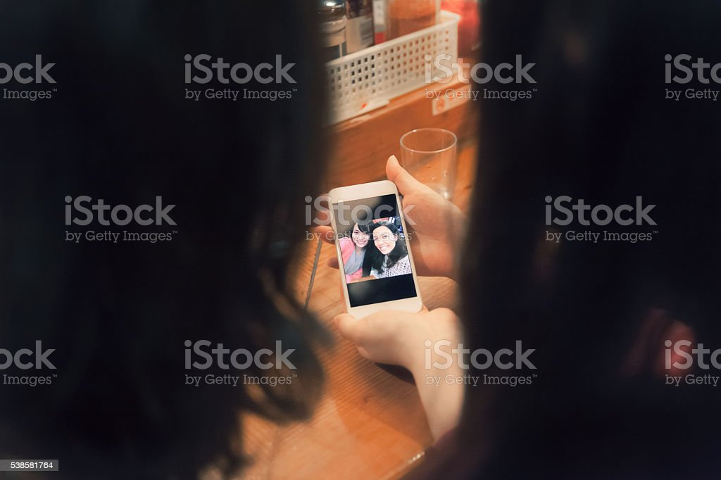 Friends looking at their selfie on a smart phone stock photo