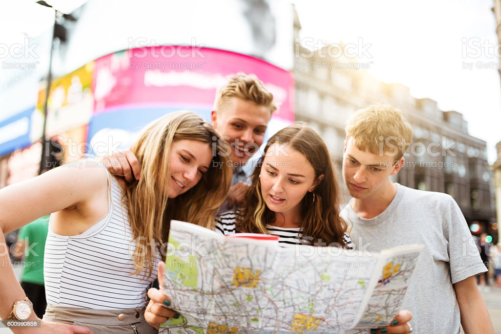 friends looking the map in piccadilly circus stock photo