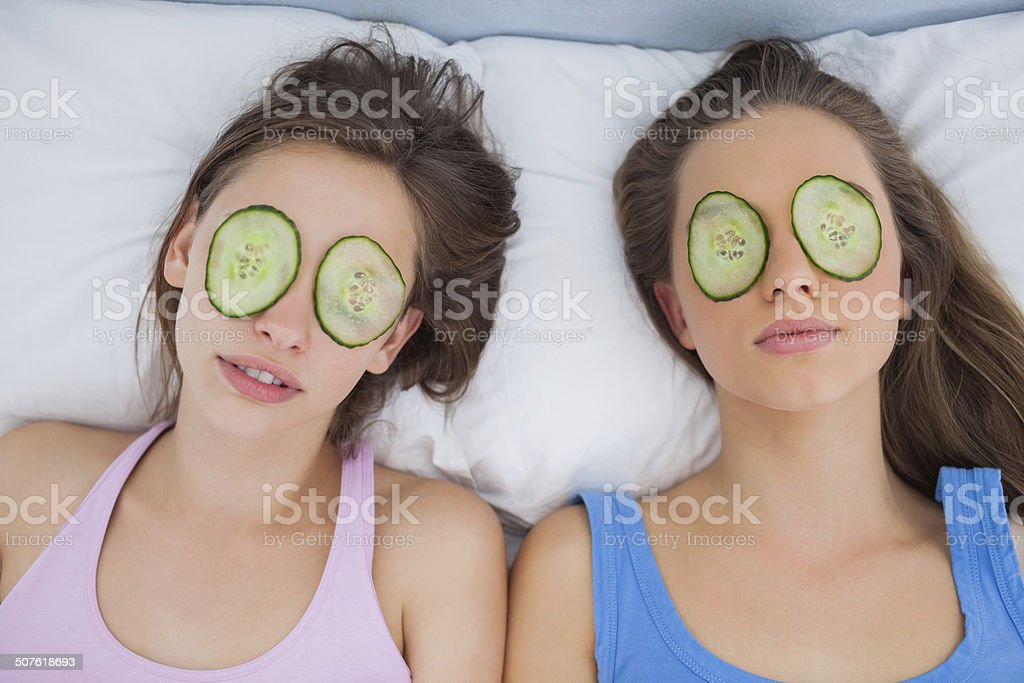 Friends lying in bed with cucumber slices on eyes stock photo