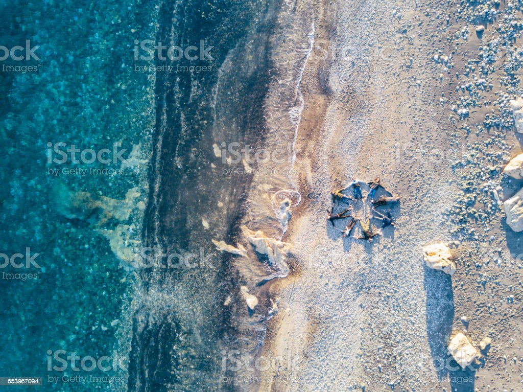 Friends lying together on the beach, making a star shape stock photo