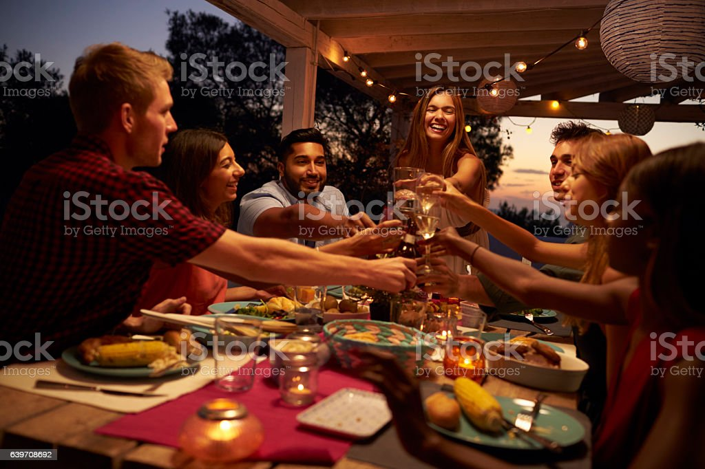 Friends make a toast at a dinner party on a patio, stock photo