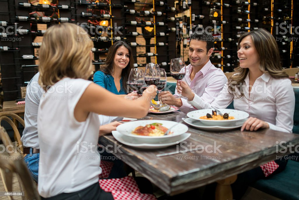Friends making a toast at a restaurant stock photo
