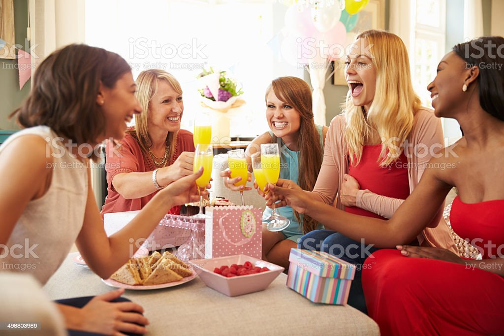 Friends Making A Toast With Orange Juice At Baby Shower stock photo
