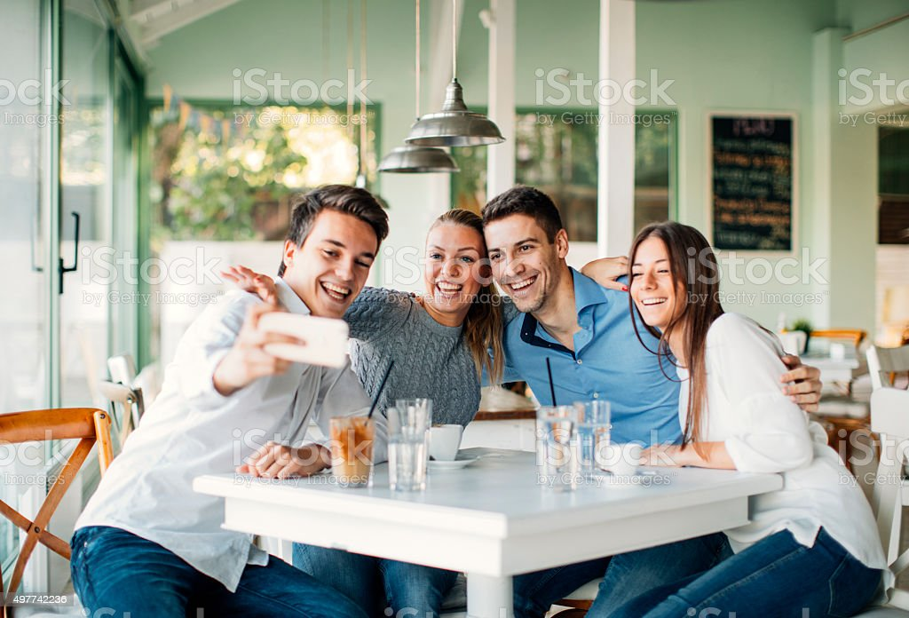 Friends Making Selfie With Smart Phone In Restaurant. stock photo