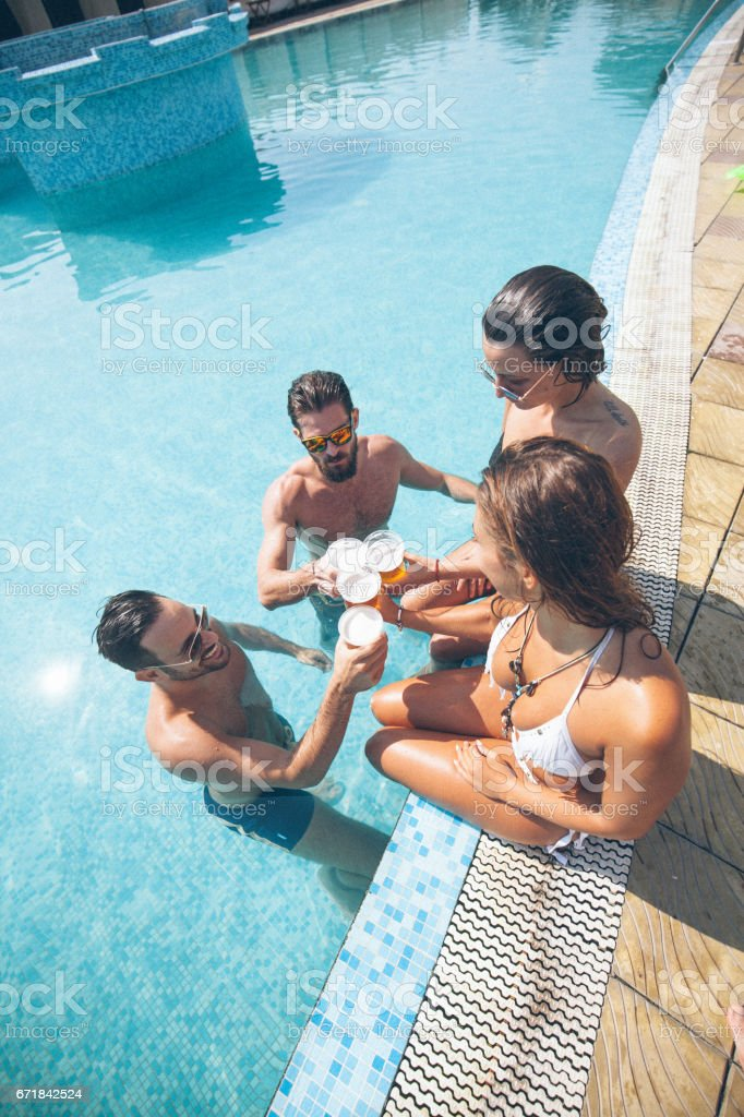 Four young and attractive friends are making toast with beer. They...