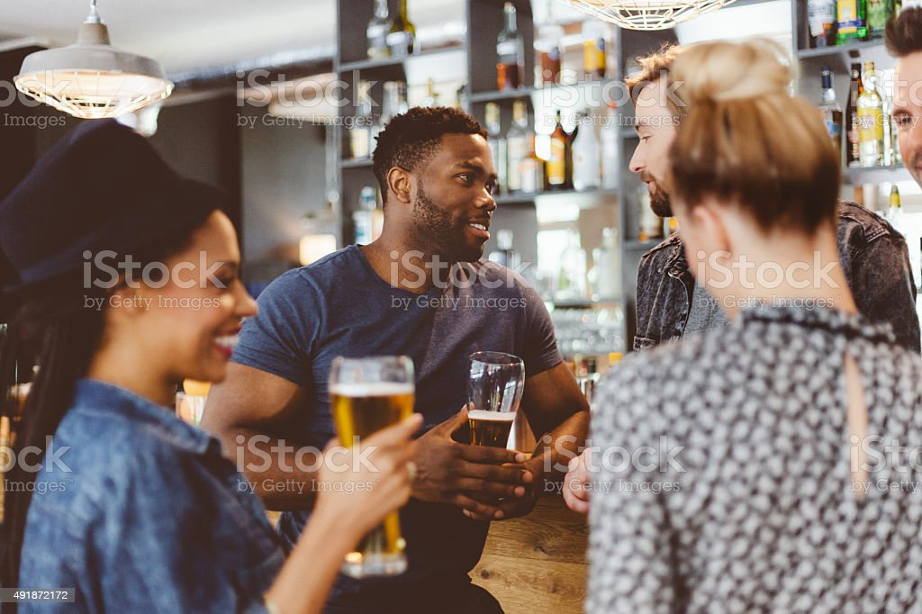 Friends meeting in a pub, drinking beer stock photo