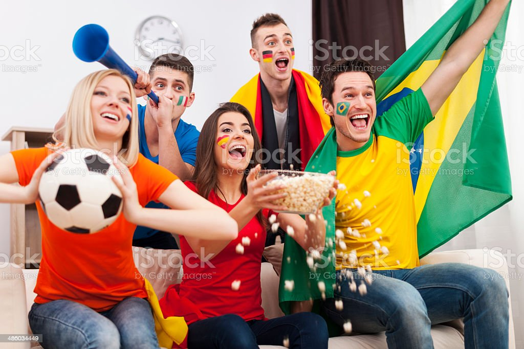 Friends of different nations celebrating goal royalty-free stock photo