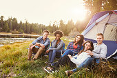 Friends on a camping trip relaxing by a tent look