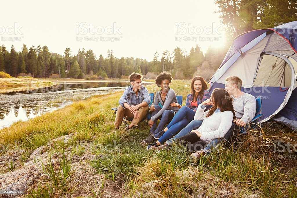 Friends on a camping trip relaxing by their tent near stock photo