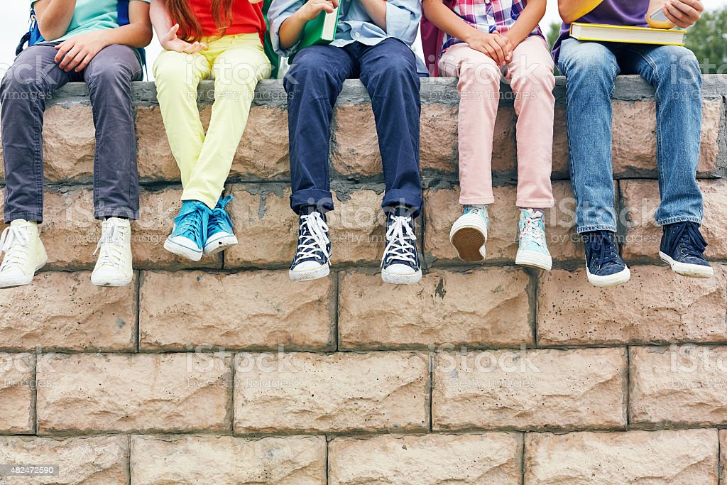 Friends on brick wall stock photo