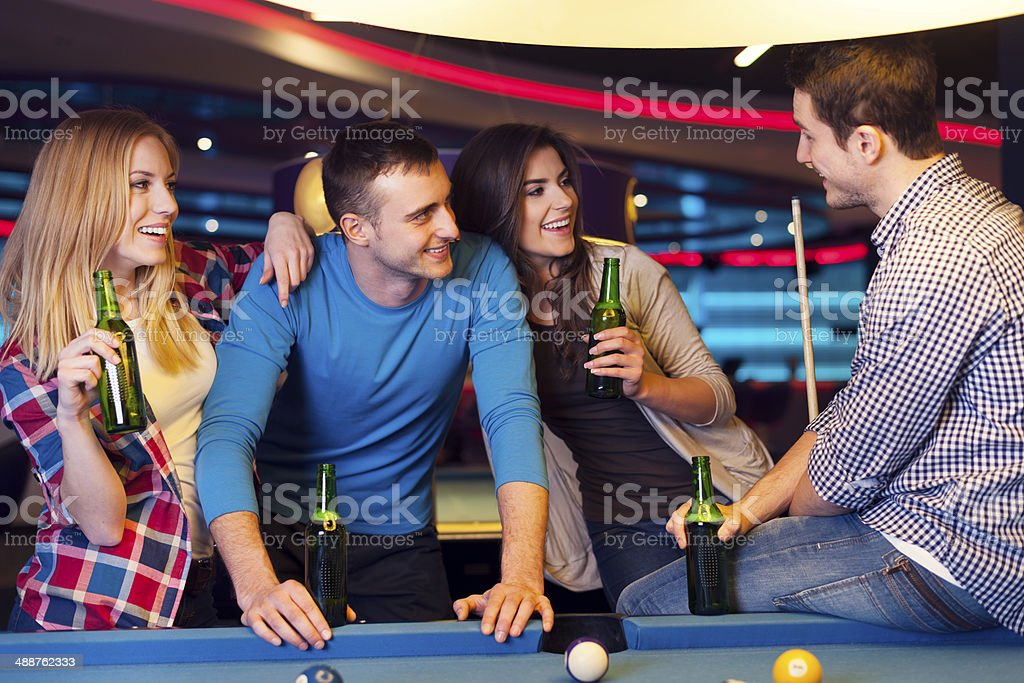 Friends on party in billiard club stock photo