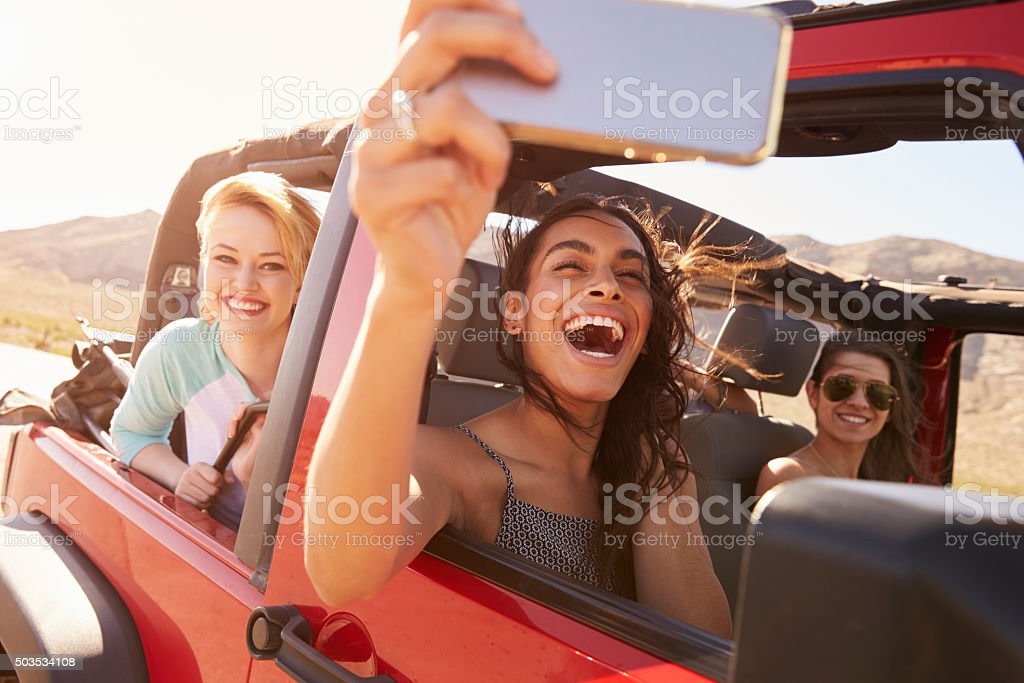 Friends On Road Trip In Convertible Car Taking Selfie stock photo