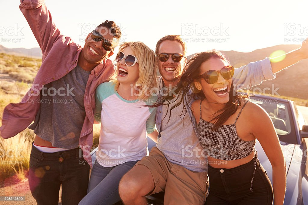 Friends On Road Trip Sitting On Hood Of Convertible Car stock photo