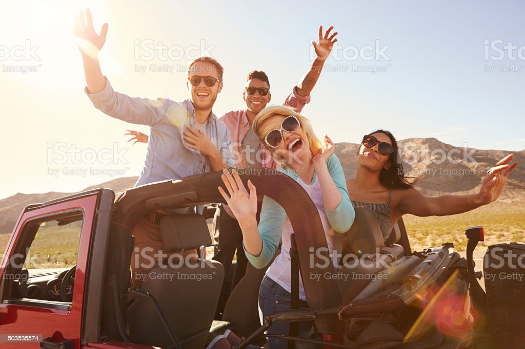 Friends On Road Trip Standing In Convertible Car stock photo