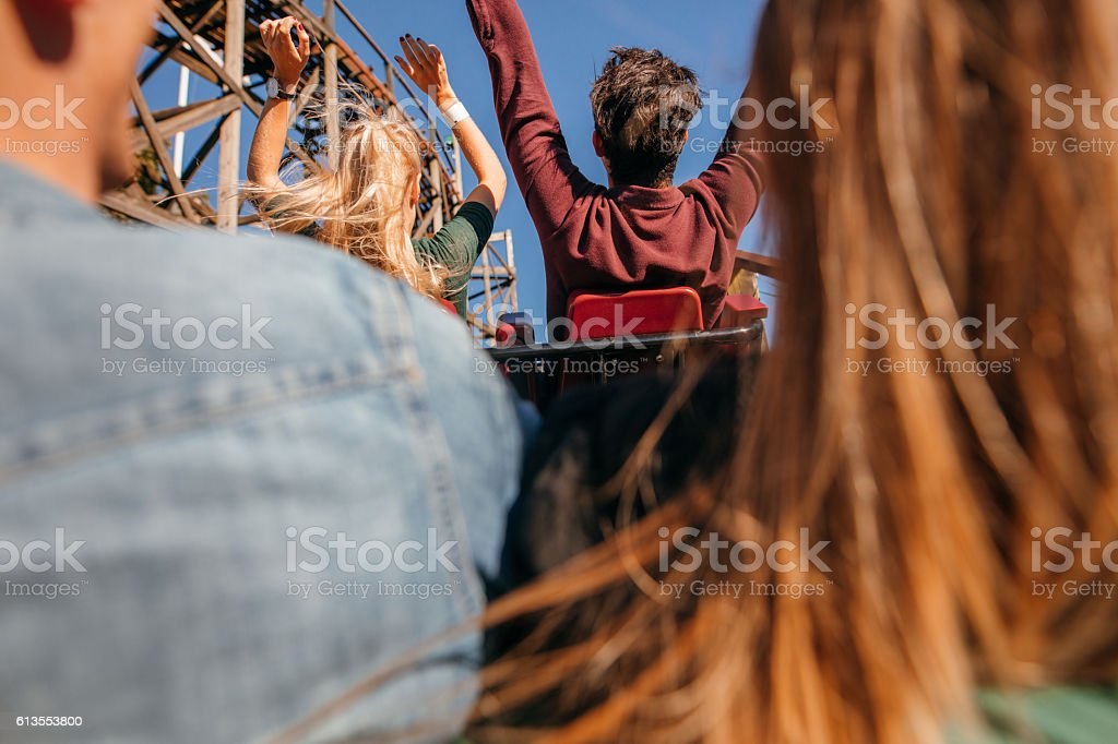 Friends on roller coaster ride at amusement park stock photo