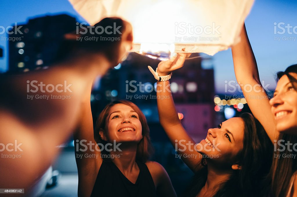 Friends on rooftop releasing paper lantern in the sky stock photo