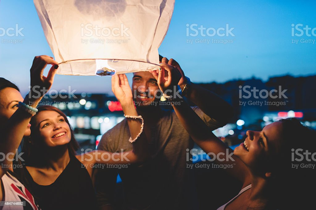 Friends on the rooftop releasing paper lantern in the sky stock photo