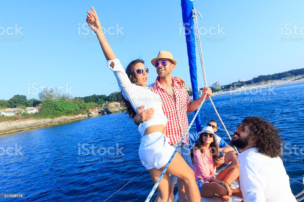 Friends on vacation with sailboat stock photo
