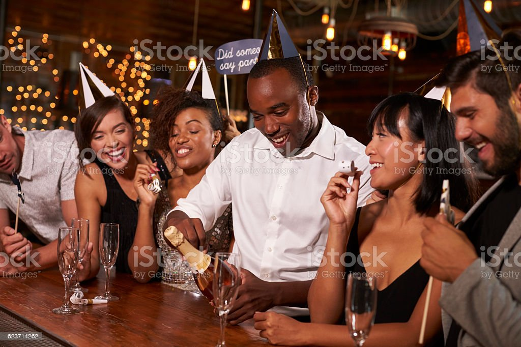 Friends opening champagne at a New Year's party at a bar stock photo