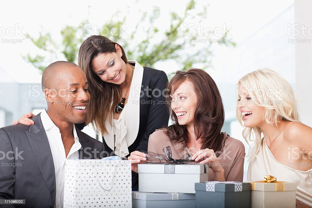 Friends opening gifts stock photo