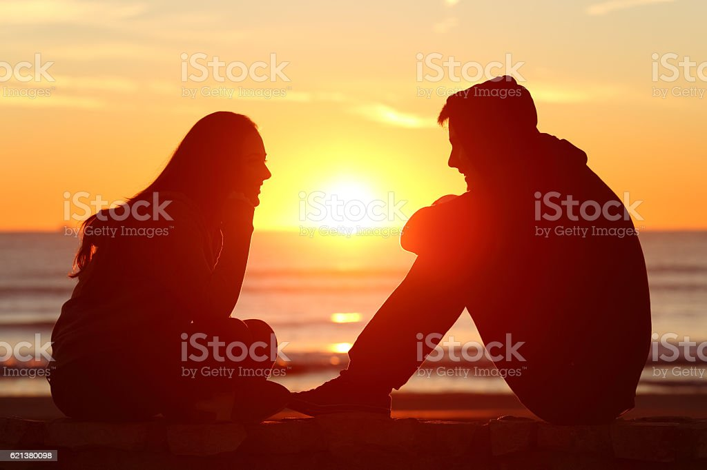 Friends or couple of teens facing at sunset stock photo