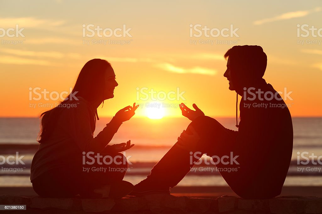 Friends or couple of teens talking at sunset stock photo