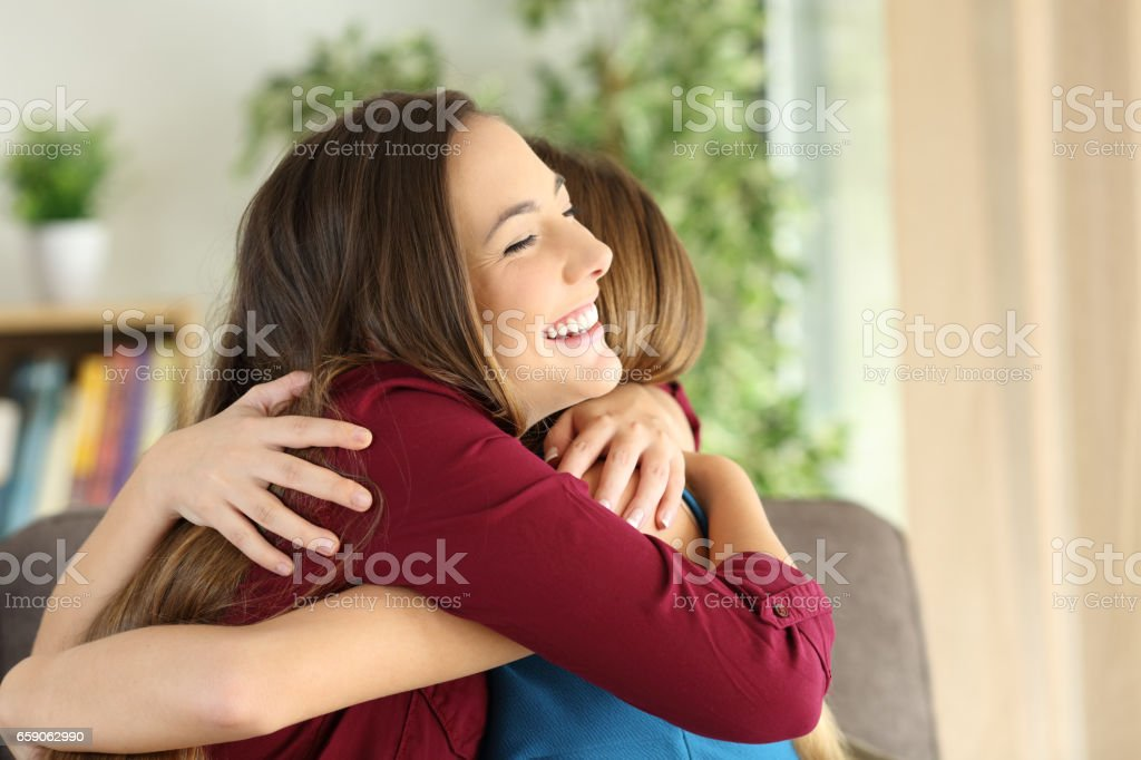 Friends or sisters embracing at home stock photo