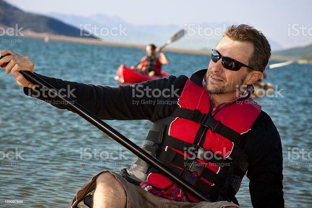 Friends paddling in kayaks on lake. Utah, USA. Mountains. royalty-free stock photo