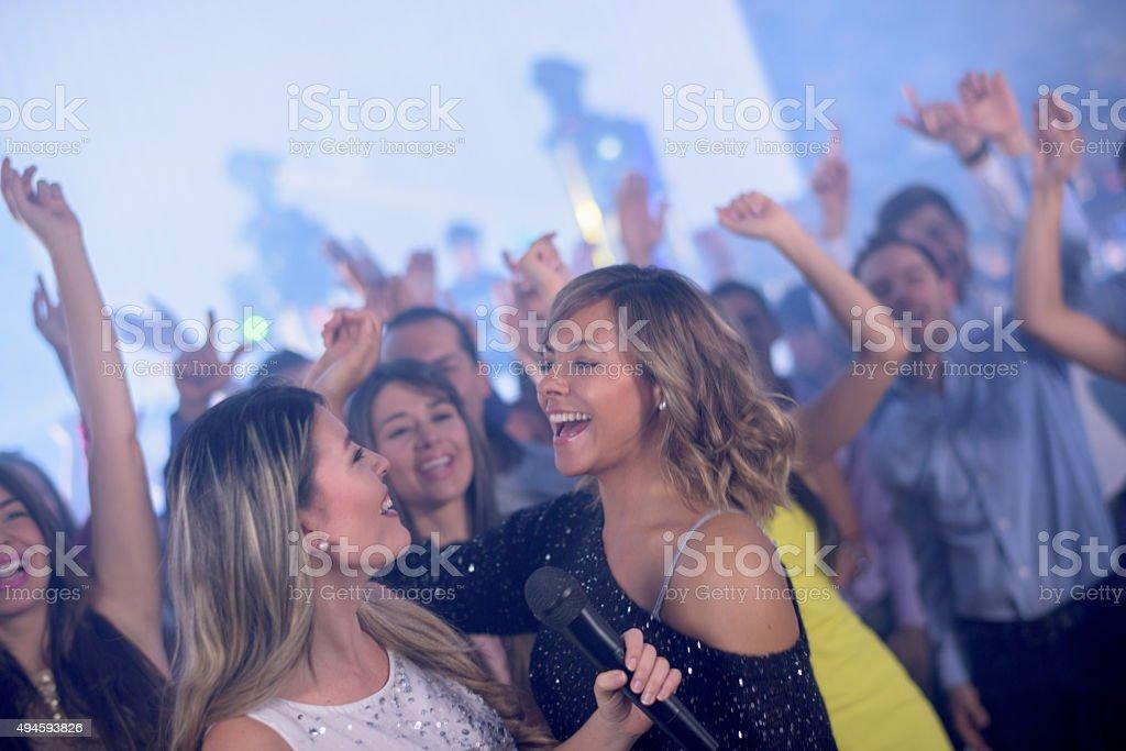 Friends partying at a karaoke bar stock photo