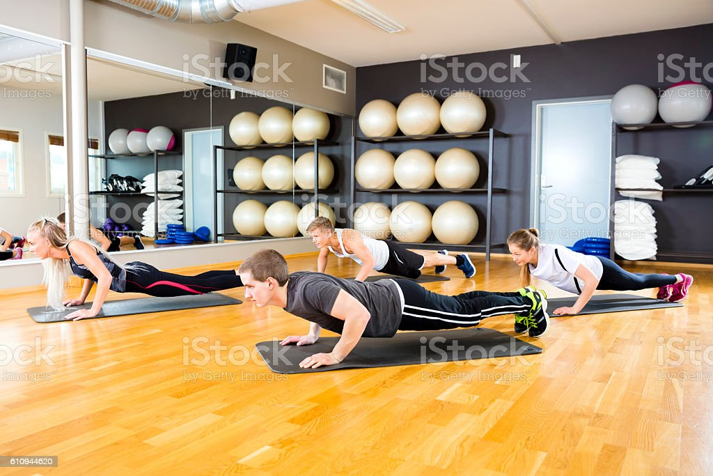 Friends Performing Pushups On Mat In Gym stock photo