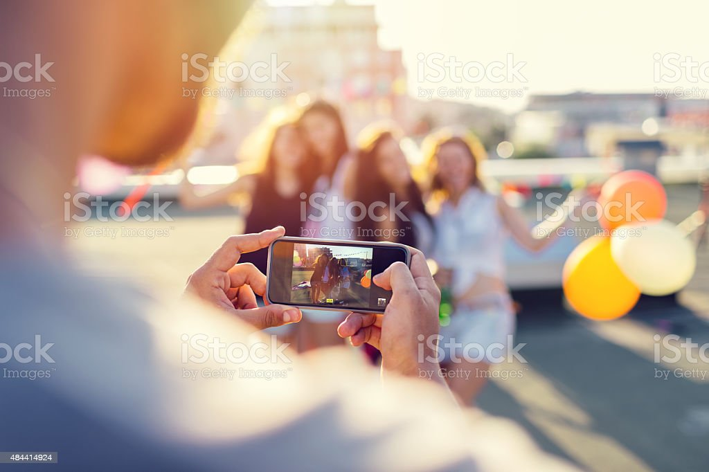 Friends photographing on the rooftop stock photo