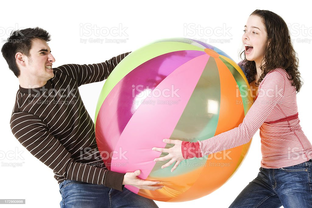 Friends play tug-of-war with a beachball royalty-free stock photo