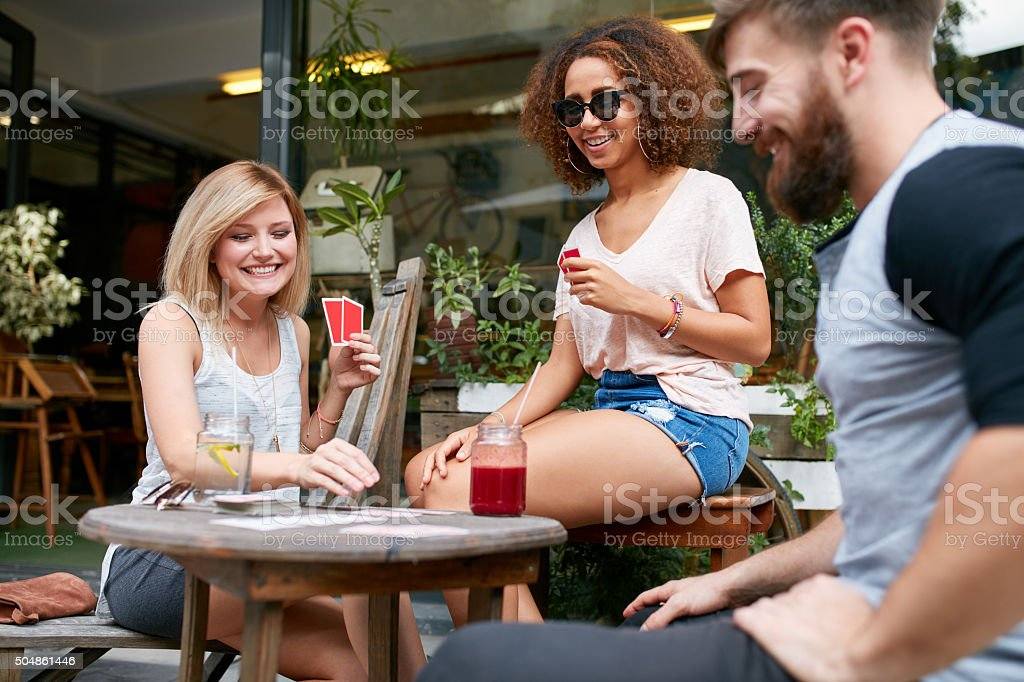 Group of friends playing a game of cards in a cafe. Woman picking up...