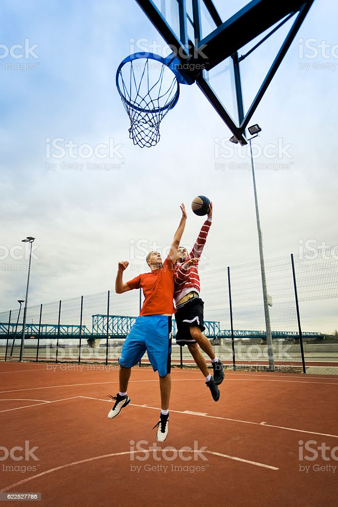 Friends playing basketball stock photo