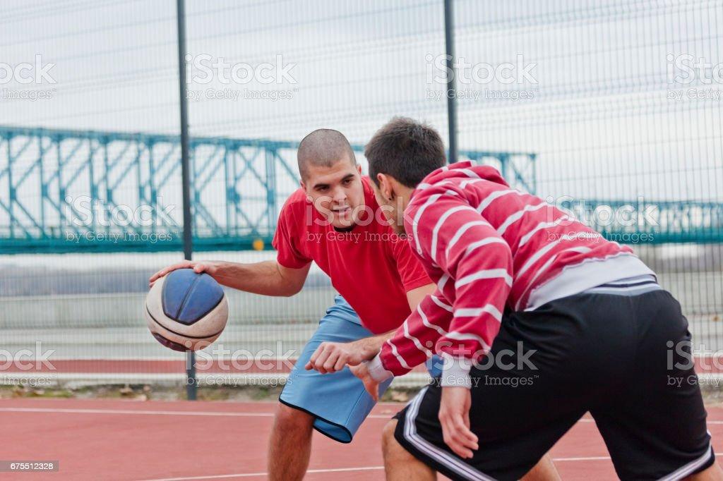 Friends playing basketball stock photo