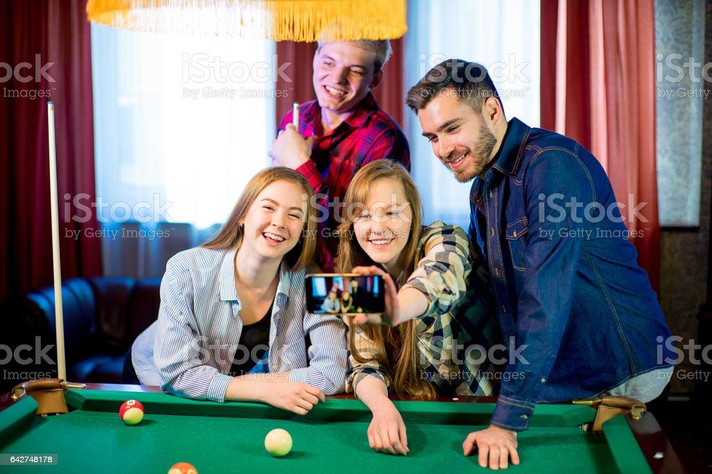friends playing billiard selfie stock photo