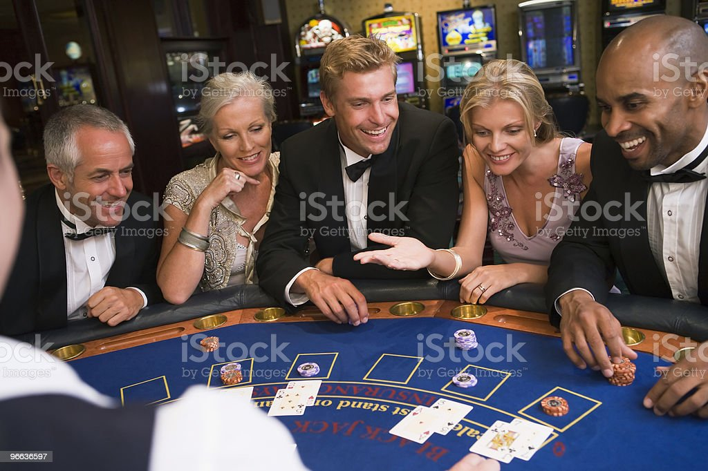 Friends playing blackjack in casino royalty-free stock photo