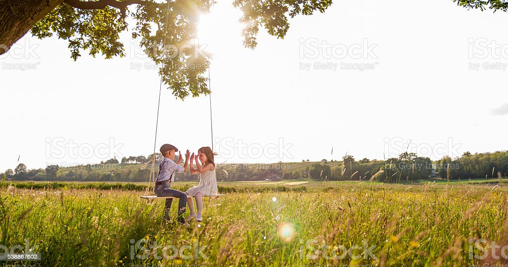 Friends playing clapping game while swinging stock photo