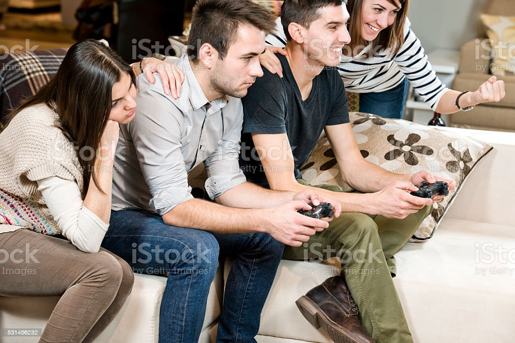 Friends playing console games stock photo