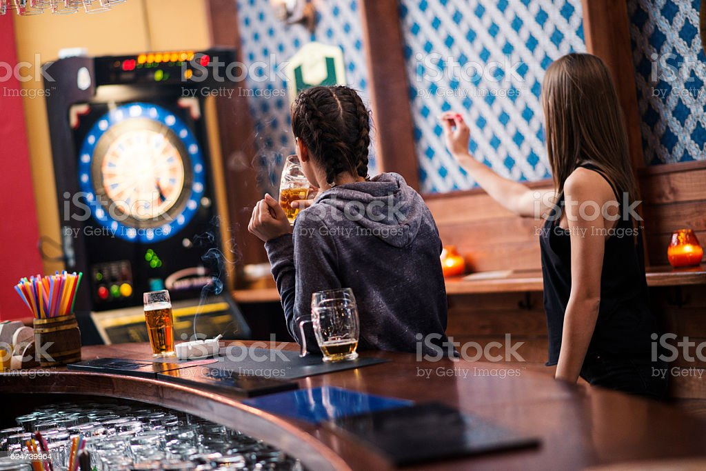 Friends playing darts in a club stock photo