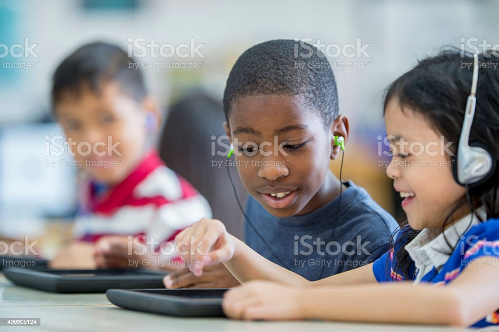 A multi-ethic group of elementary age children are sitting in the...